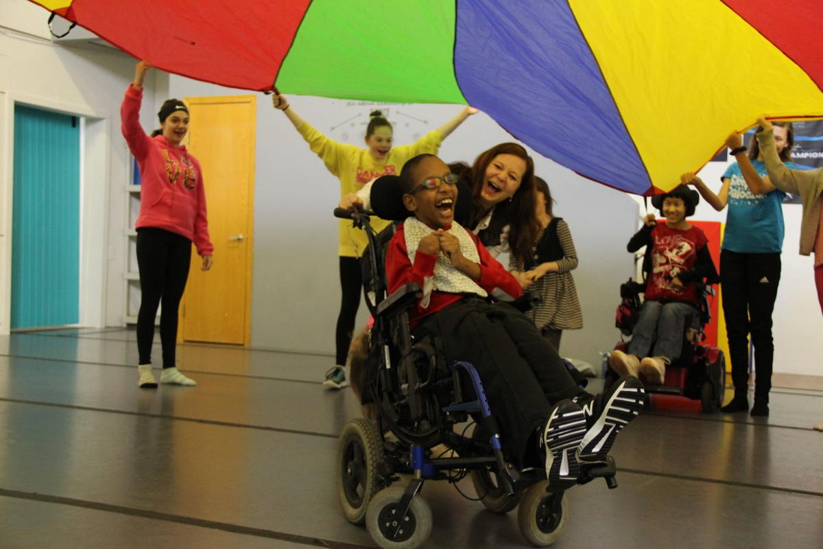 Tariku Antoine smiles as he plays under a parachute March 30 with teacher Karen Larson during a Darby's Dancers class inRamsey. Photo by Paige Kieffer